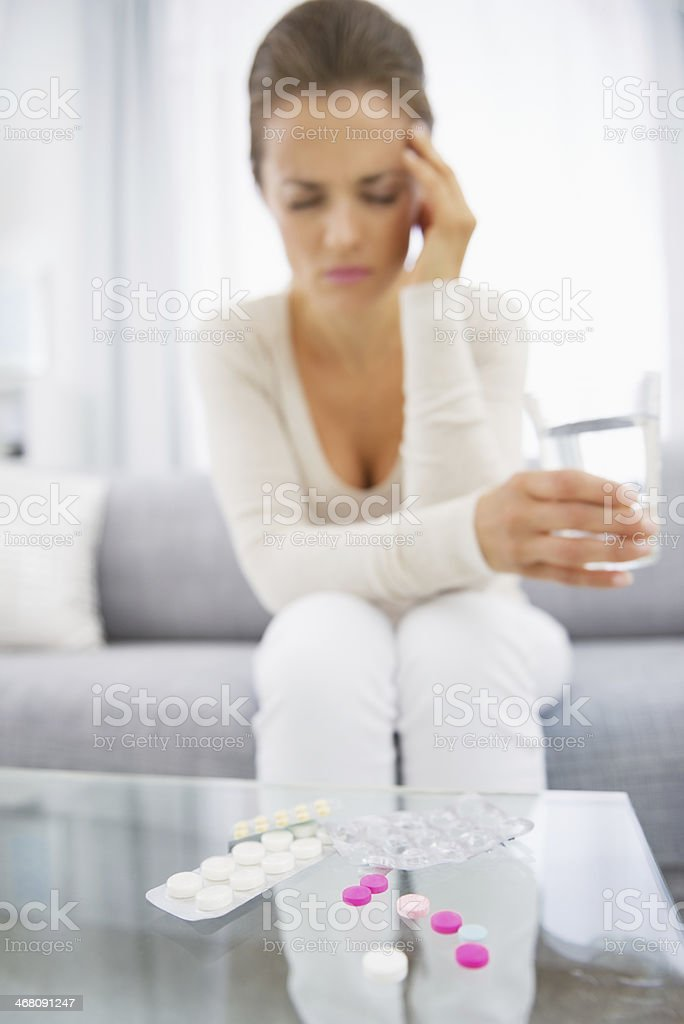 closeup on pills and feeling bad young woman in background royalty-free stock photo