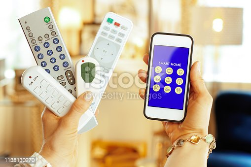 istock Closeup on remote controls and smartphone with smart home app 1138130270
