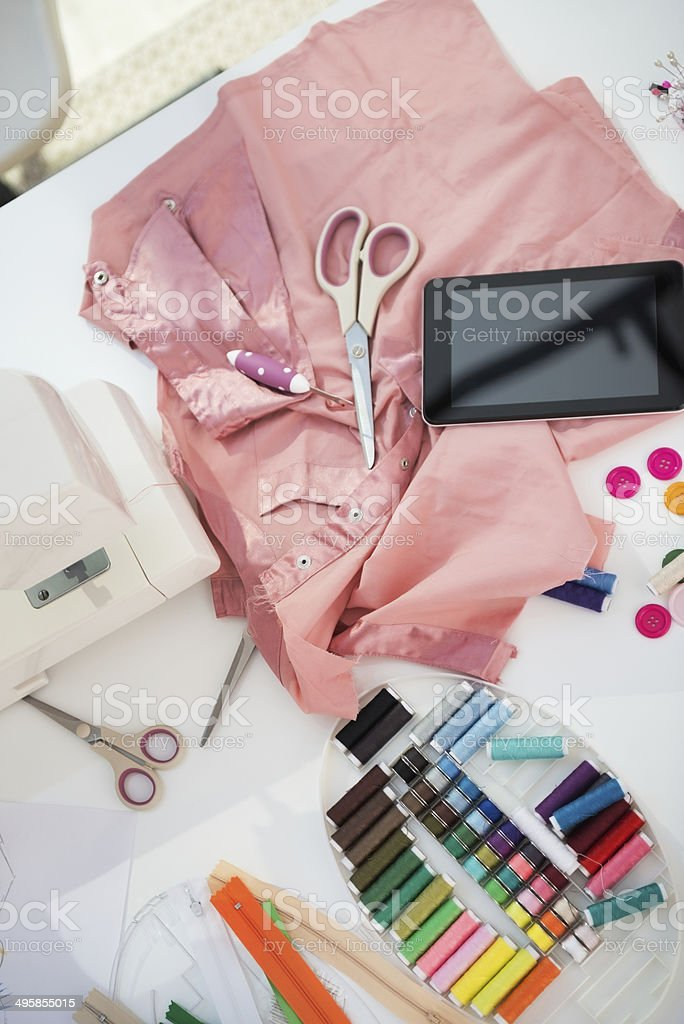 closeup on seamstress table with tablet pc stock photo