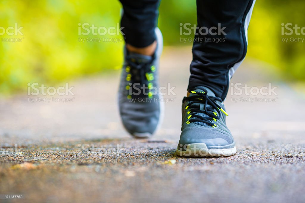 Closeup on shoe of athlete runner man feet running on road