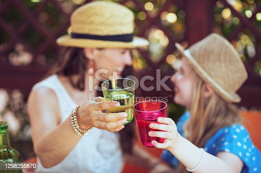 istock Closeup on smiling family clinking glasses 1298255870