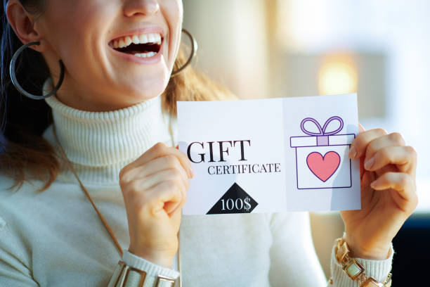 Closeup on smiling modern woman holding gift certificate stock photo