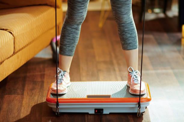 Closeup on sports woman training using vibration power plate stock photo