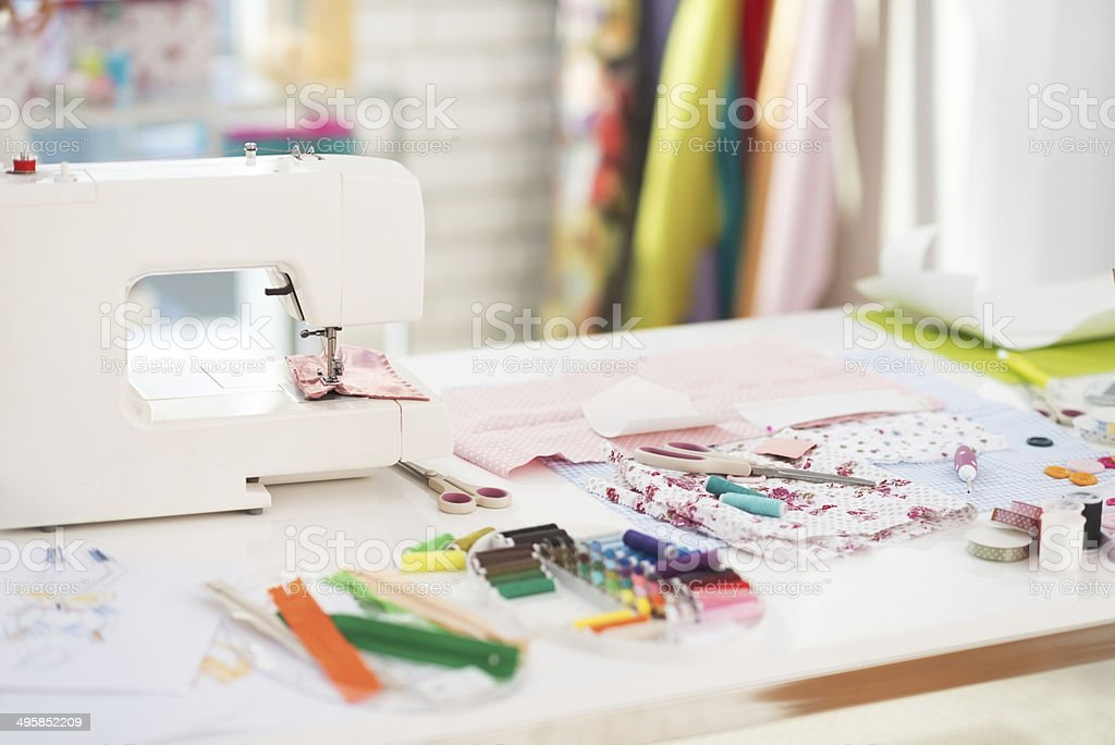 closeup on table of seamstress with scissors threads and fabric stock photo