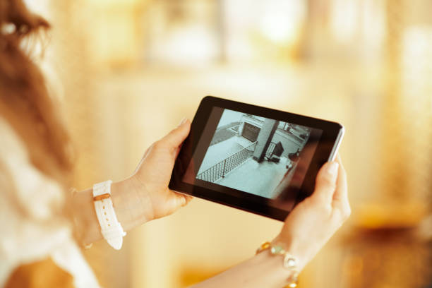 Closeup on tablet PC with video from camera in hands of woman Closeup on tablet PC with video from security camera in hands of modern housewife at home. touchpad stock pictures, royalty-free photos & images