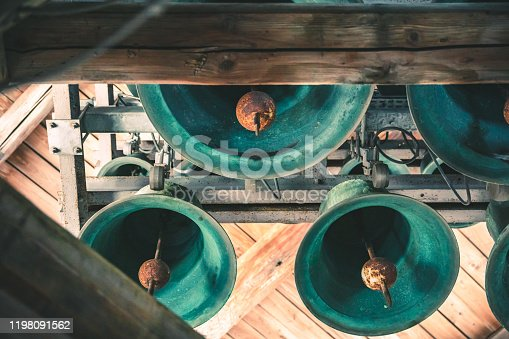 Details on the large and very old bells hanging on wooden beams from the steeple of Basilica Notre Dame de Fourviere, in one of the bell tower. They are still in use and active. The Basilica was built between 1872 and 1884 with Byzantine and Romanesque architecture style, in a dominant position overlooking the city of Lyon, and dedicated to the Virgin Mary. It features fine mosaics and superb stained glass very ornate with gold and some paintings on the ceiling. This image was taken inside this famous place of worship monument in Lyon city, in Rhone department, Auvergne-Rhone-Alpes region in France (Europe), on Fourviere hill.