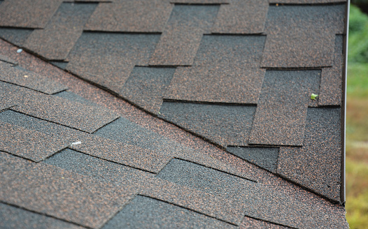 A close-up on the problem, critical area of a roof valley and drip edge covered with asphalt dimensional shingles above metal roof flashing.