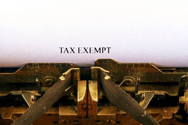 Closeup on vintage typewriter. Front focus on letters making TAX EXEMPT text. Business concept image with retro office tool stock photo