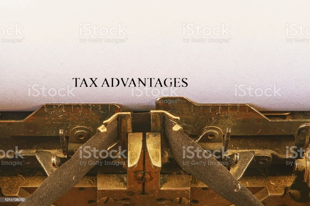 Closeup on vintage typewriter. Front focus on letters making TAX ADVANTAGES text. Business concept image with retro office tool stock photo