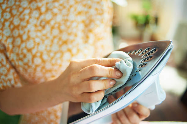 Closeup on woman cleaning iron with cloth stock photo