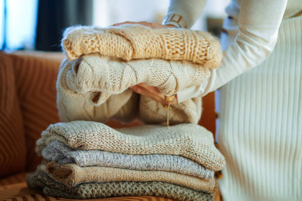 Closeup on woman near couch folding sweaters for storage stock photo