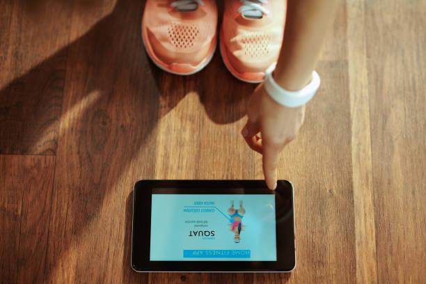 närbild på kvinna som använder hem tränare app i tablet pc - calendar workout bildbanksfoton och bilder