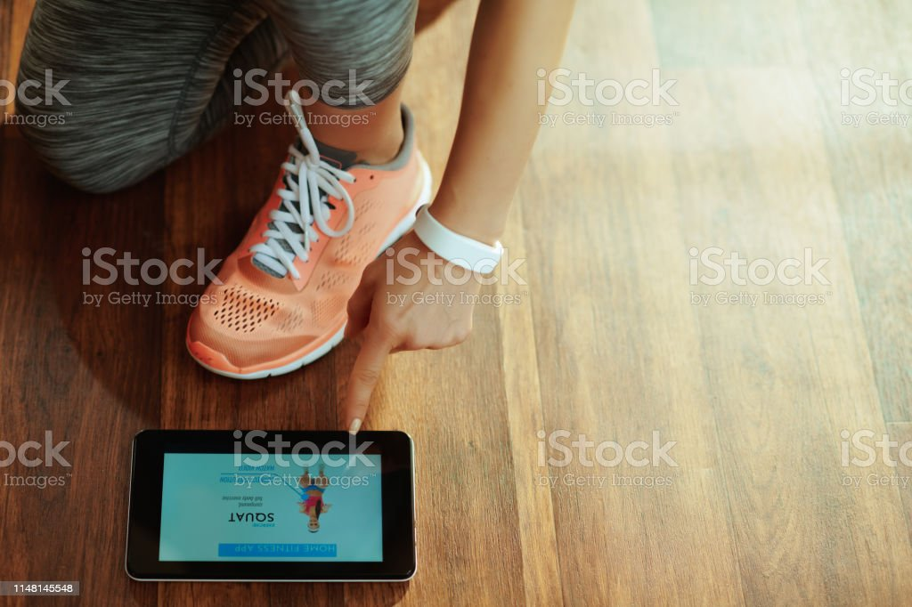 Closeup on healthy woman in sport clothes at modern home using online...