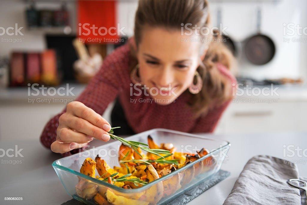 closeup on young housewife adding rosmarinus to baked pumpkin stock photo