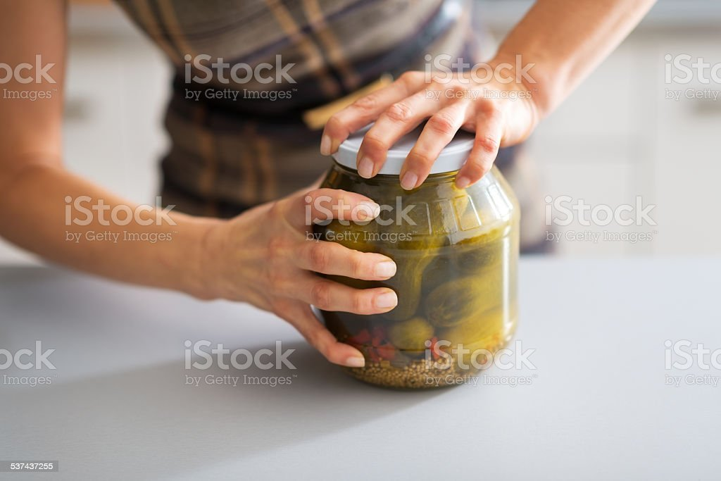 closeup on young housewife opening jar of pickled cucumbers stock photo