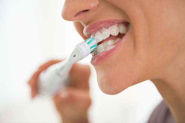 closeup on young woman brushing teeth stock photo
