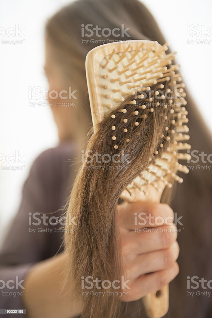 closeup on young woman combing hair stock photo