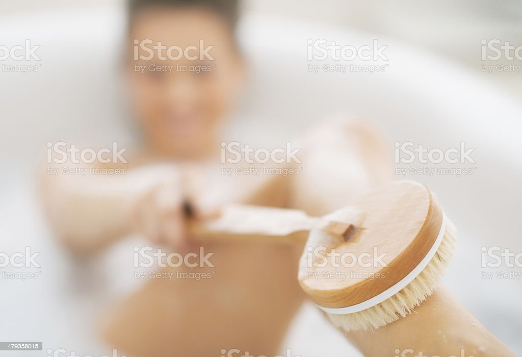 closeup on young woman in bathtub using body brush stock photo