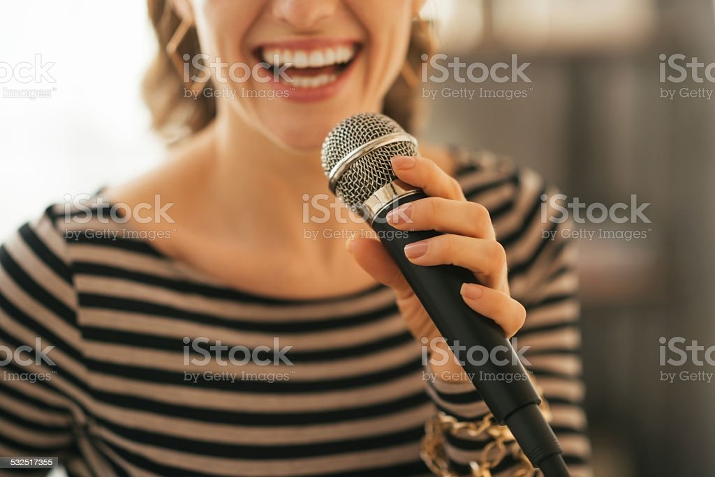 closeup on young woman singing with microphone in loft apartment stock photo