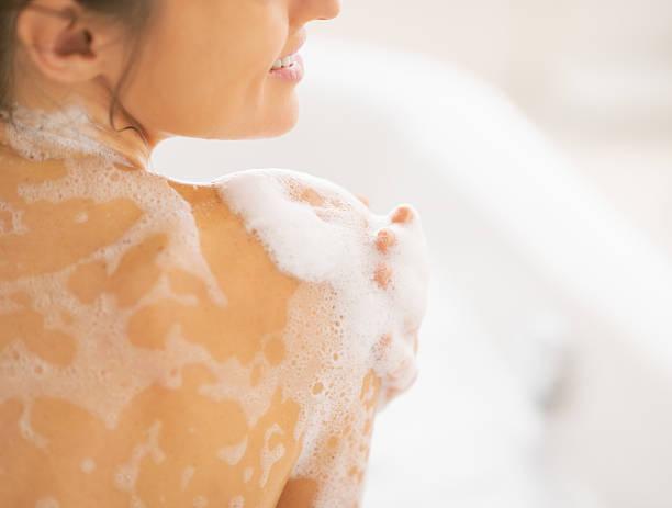 primo piano del giovane donna lavaggio in bathtub. vista posteriore - il corpo umano foto e immagini stock