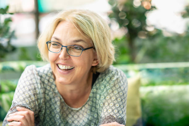 Closeup outdoor nature portrait of blond happy smiling mature woman in her fifties wearing glasses. stock photo