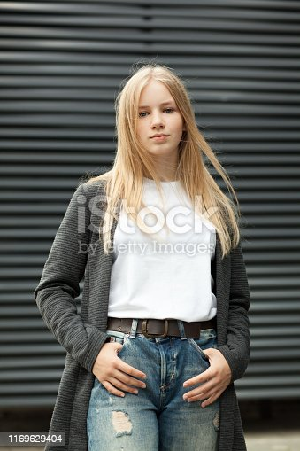 Close-up outdoor portrait of a 13 year old blonde teenage girl in a gray jacket and jeans