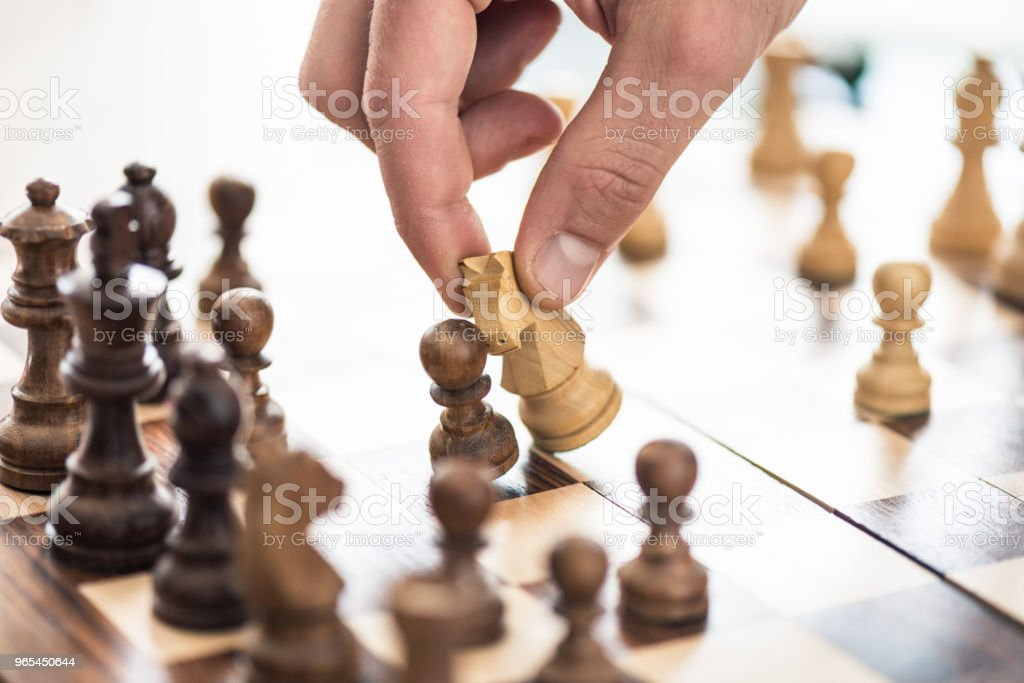 close-up partial view of human hand playing chess zbiór zdjęć royalty-free
