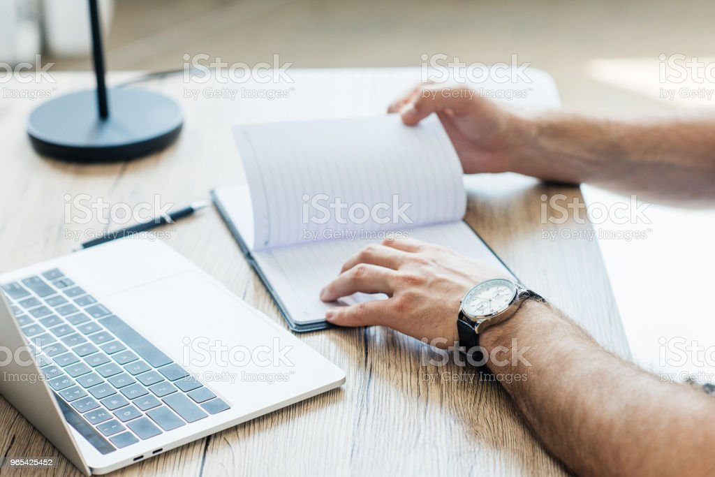 close-up partial view of person holding blank notebook at workplace zbiór zdjęć royalty-free