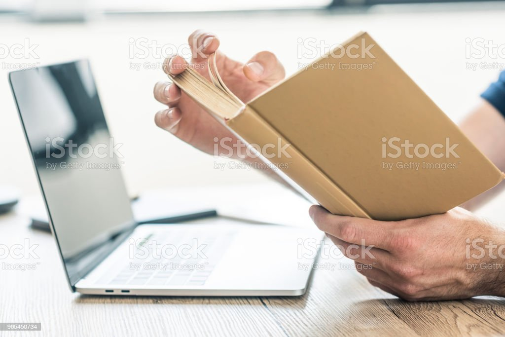 close-up partial view of person holding book at table with laptop royalty-free stock photo
