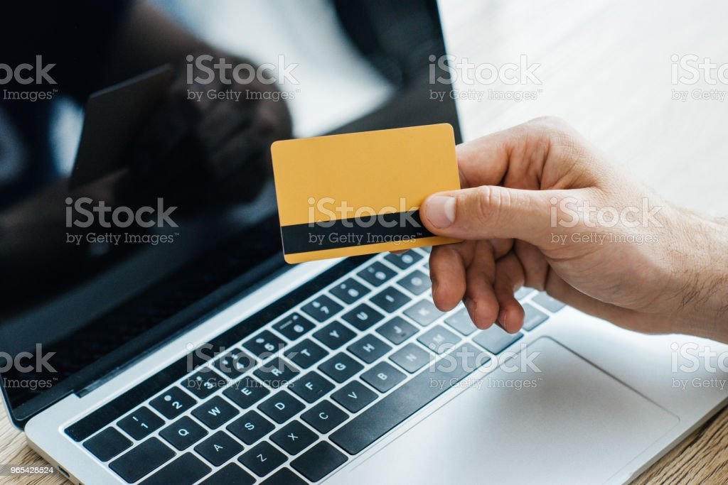 close-up partial view of person holding credit card near laptop royalty-free stock photo