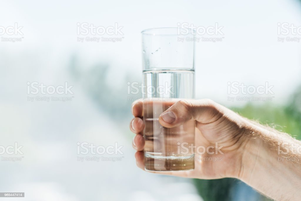 close-up partial view of person holding glass of fresh water royalty-free stock photo