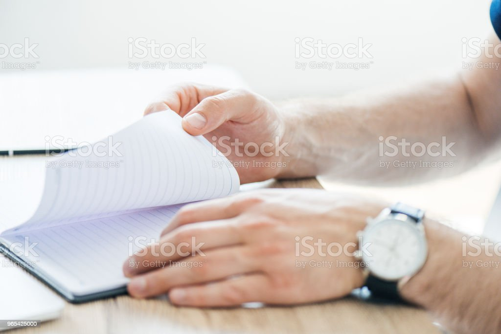 close-up partial view of person holding notepad at workplace zbiór zdjęć royalty-free