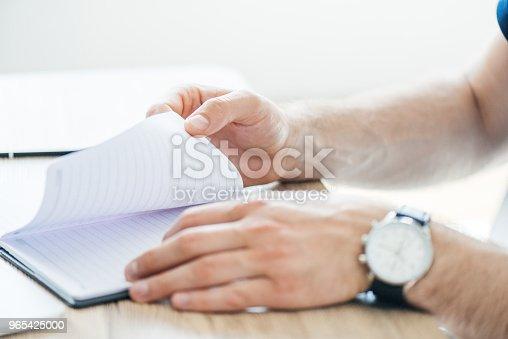 Closeup Partial View Of Person Holding Notepad At Workplace - Stockowe zdjęcia i więcej obrazów Biznes