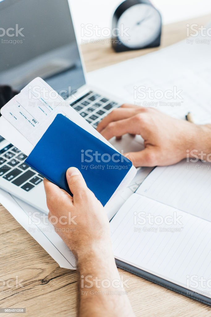 close-up partial view of person holding passport with tickets and using laptop royalty-free stock photo