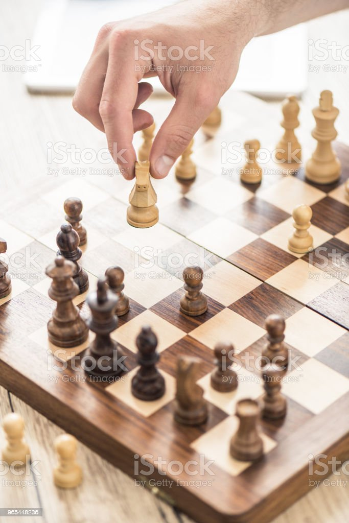 close-up partial view of person playing chess at wooden table zbiór zdjęć royalty-free