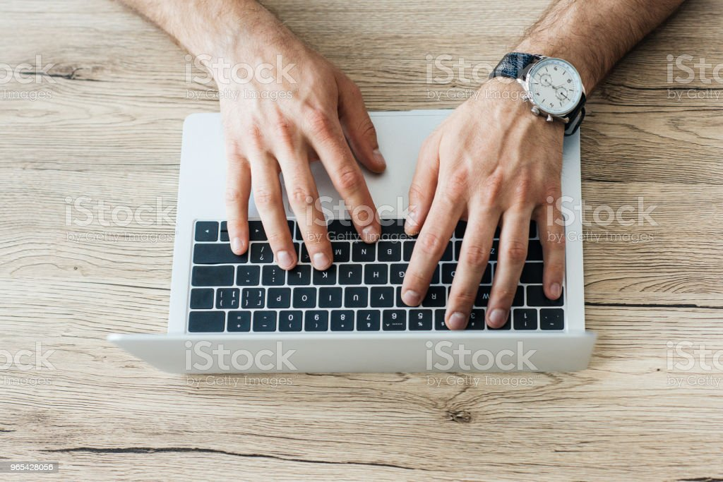 close-up partial view of person typing on laptop at wooden table royalty-free stock photo