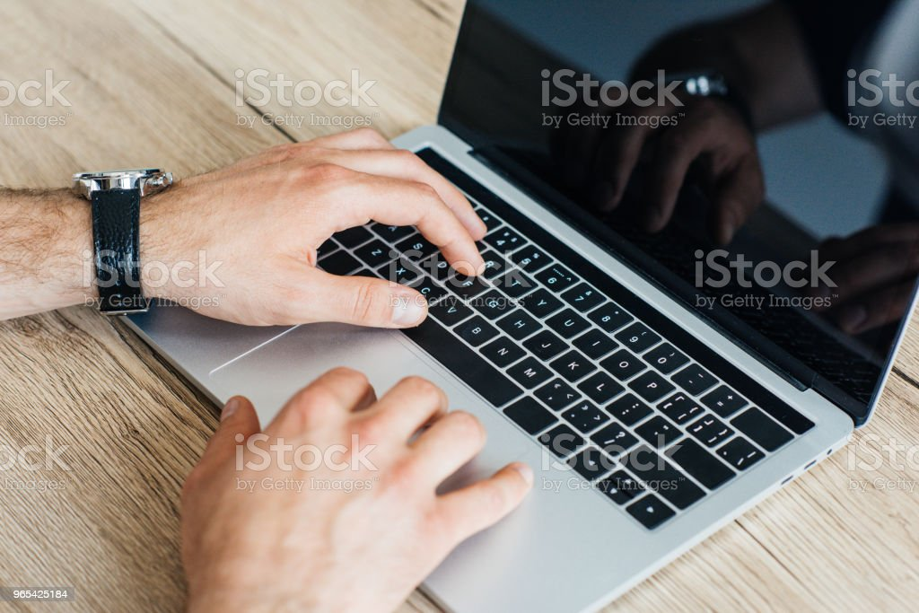 close-up partial view of person typing on laptop with blank screen zbiór zdjęć royalty-free