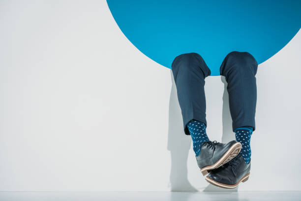 close-up partial view of stylish man falling into hole on grey - shoes fashion stock photos and pictures