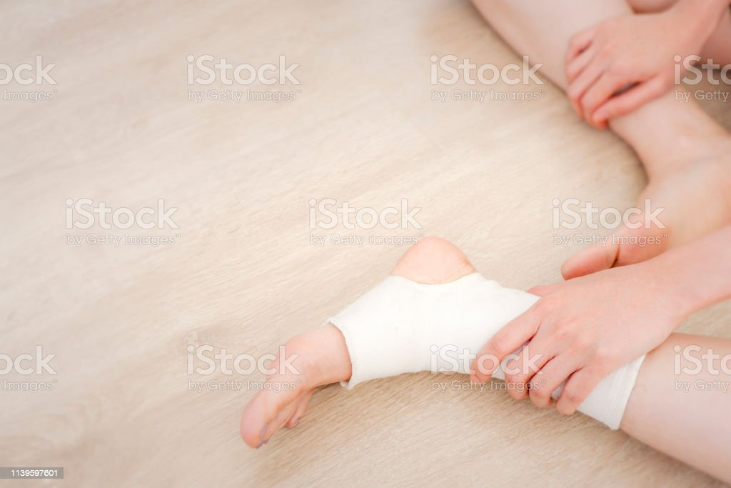 Closeup People of a Foot with White Gauze Elastic Bandage. Hands on...