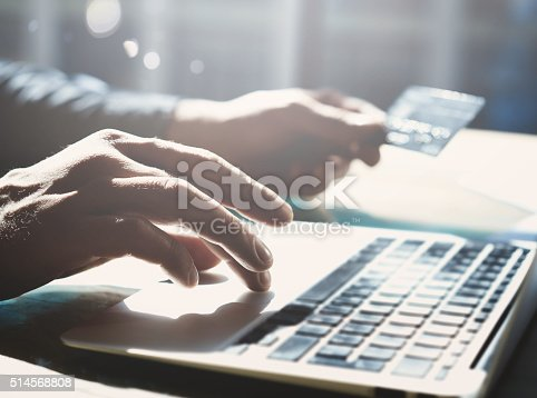 Closeup photo businessman working with generic design notebook. Online payments, banking, hands keyboard. Blurred background, film effect.