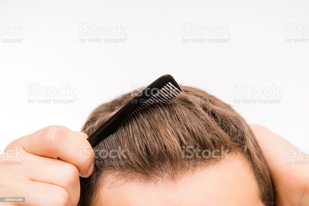 Close-up photo of a amn brushing his hair stock photo