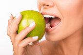 Closeup photo of a beautiful healthy girl biting an apple