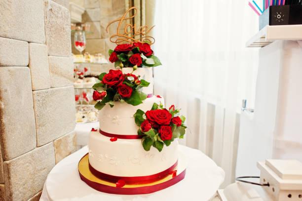 nahaufnahme foto von einem großen weißen und roten hochzeitstorte dekoriert mit frischen roten rosen. - orange hochzeitstorten stock-fotos und bilder