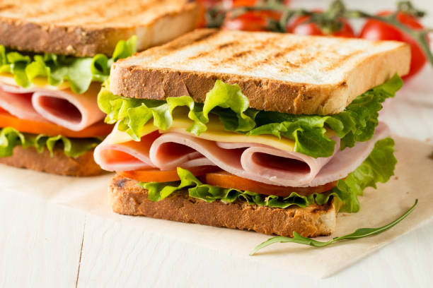 close-up photo of a club sandwich. sandwich with meat, prosciutto, salami, salad, vegetables, lettuce, tomato, onion and mustard on a fresh sliced rye bread on wooden background. olives background. - panino ripieno foto e immagini stock