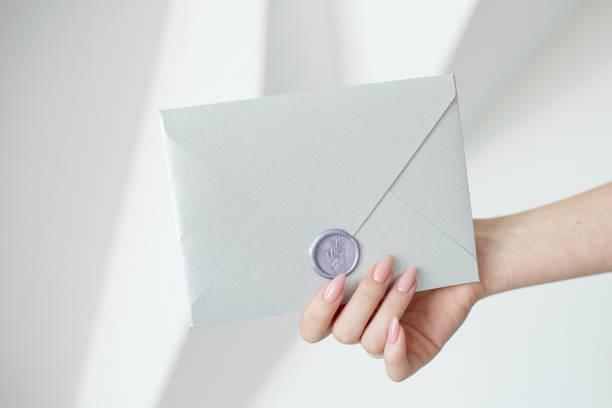 클로즈업 사진 여자의 손에 들고 핑크 초대장 봉투는 왁 스로 밀봉, 상품권, 카드, 결혼식 초대 카드 - 초대장 뉴스 사진 이미지