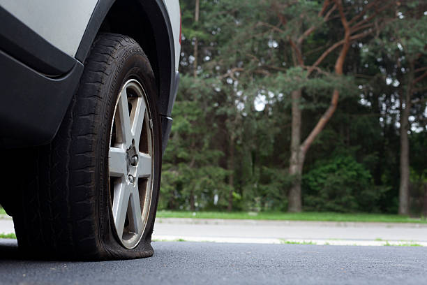 Close-up photo of a flat tire on a car on a road stock photo