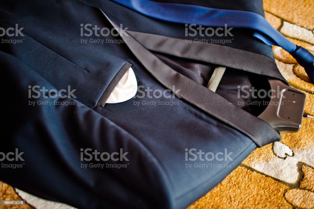 Close-up photo of a groom\'s suit or tuxedo on the hanger laying in...