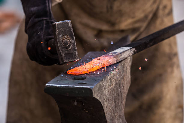 Close-up photo of a hammer striking a heated piece of metal stock photo
