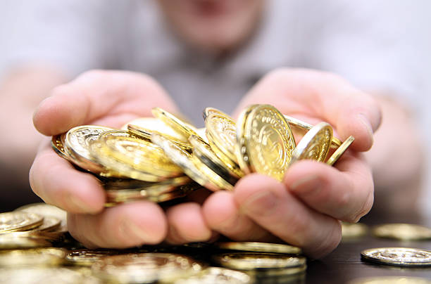Close-up photo of a handful of gold coins stock photo