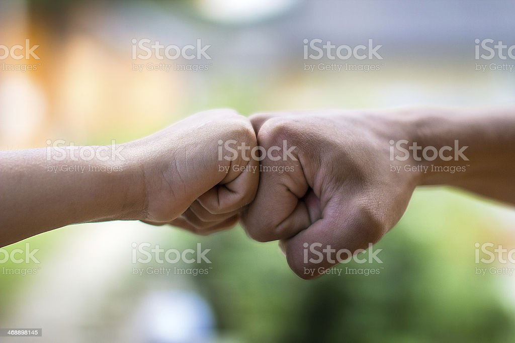 Close-up photo of a man and boy fist bumping stock photo